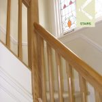 Handrail running between square newel posts, spindles are square, chamfered at picth.